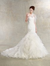 Aria Style #K1222 Sweetheart organza mermaid gown with ruched bodice and ruffled skirt. Dropped waist highlighted by flower and beading detail. Detachable matching one shoulder lace jacket available.