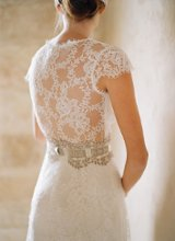 BRIGITTE-back  <br /> Silk white cap sleeved V-neck lace gown with silver guipure belt over full lace skirt lined in pearl silk.