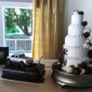 Five (5) tier muddy wedding cake; white almond wedding cake; adorned with chocolate and white chocolate strawberries; . Grooms cake; chocolate with chocolate ganache on top replica of grooms original truck, bride and grooms cake topper with bride dragging groom