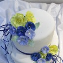 Pretty wedding cake with all edible flowers. Yellow roses and blue delphiniums. Venue: Ancaster Mill