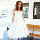 <br /> <b>Jessie</b> <br /> <br /> Jessie is an adorable strapless dupioni silk tea-length wedding gown – featuring a flattering rusched bodice that sits at the top hip while hand made silk flowers accentuate the waist. A tiny tulle ruffle peeks out from under the full dupioni skirt. Delicate silk buttons extend the length of the bodice.  <br /> <br /> Jessie is available in white, off white, ivory, champagne or blush