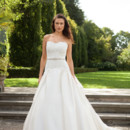 Viola Abundant with hand-cut French Alencon lace and accented by a glittering belt, this wedding gown's bodice extends a sophisticated length. Cleverly gathered to flatter, Viola's magnificent A-line skirt blooms from the hip and flows into a dramatic sweep train. Shown in ivory dupioni with off white lace.
