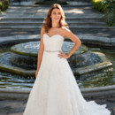 Penny Abloom with French Alencon lace, Penny is enchanting. This A-line wedding gown's magic has everything to do with simplicity. Other than a gleaming, hand-beaded belt and covered buttons, Penny is unadorned from sweetheart neckline to classic sweep train.