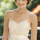 Camille A charming illusion of sheer English net and French lace applique, Camille's sweetheart bodice and deep V-back set a glamorous tone. Crowned by a wide belt, a removable overskirt of pleated silk organza amplifies the drama of the fluted lace skirt.