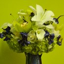 A bouquet of white lilies, calla lilies, and green cymbidium orchids, and green hydrangeas with a touch of dark blue delphinium.