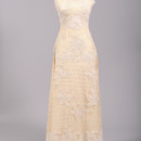 1960's Lace Jeweled Vintage Wedding Gown Designed in the 60's this magnificent vintage wedding gown is a true work of art and is done in a sheer floral lace embroidered appliqued net with hand sewn encrusted pearls and sequins throughout over an attached silk blend lining. The bodice features a pearl and sequin encrusted lace embroidered appliqued high collar neckline which works it's way around the shoulder to the back with a scalloped shawl. The sheer net offers vertical rows of tiny pearls in the front. The ecru silk blend lining can be seen through the sheer net and offers wide straps a scooped neck line and high back. The skirt of this A-line sheath gown offers slight gores and finishes at the floor with scalloped appliques. A concealed metal zipper and 26 self covered buttons enclose this gown in the back. http://www.millcrestvintage.com/vintage-wedding-dresses/1960s-lace-jeweled-vintage-wedding-gown