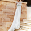 Destination Romance STYLE DR187 Chiffon gown with a Sweetheart neckline and sleeveless sheer beaded overlay with a low V-back and buttons. Flowing A-line skirt features a Chapel train.