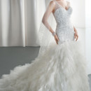 Ilissa Style No. 537 Beaded fit and flare wedding gown with a v-neckline and low v-back. The skirt on this bridal dress features layers of ruffled tulle and an attached train.