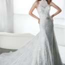 Ultra Sophisticates Style 1442 Lace, Sheath wedding gown with a high, sheer halter neckline and dramatic T-back. This bridal dress features a jeweled medallion on waist and an attached train.