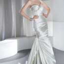 GR232 Satin, One-shoulder with asymmetrical ruching and a sweetheart neckline. Crystal jewelling flows asymmetrical throughout neckline and corset back. Skirt features a side drape with jeweled applique, a bubble hem and attached train. Available in white and ivory.
