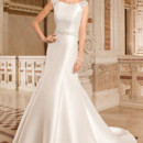 3210 Chic, sleeveless mikado modified a-line gown with boat neckline features clusters of sparkling beading on shoulders that flow into plunging low back. Waist is finished with beaded trim and bow on back.