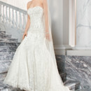 211 This sophisticated form fitting beaded lace gown features intricate beaded embroidery on the bodice, low v back and a chapel train.