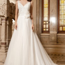 267 This romantic, soft tulle sleeveless, a-line gown features a v-neckline and low v back. The bodice is adorned with delicate lace and flowers on the waist. The tulle skirt flows into a chapel length train.