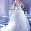 548 Strapless Tulle bridal gown with a Sweetheart neckline elaborate jeweled embroidery on bodice and lace-up back. This wedding gown features a Basque waist and multi layered handkerchief full skirt with sprays of beading and attached Chapel train.