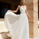 205 Chiffon, A-line destination wedding gown with spaghetti straps, asymmetrical ruching on bodice and beaded band on waist. The skirt on this bridal dress features a Chapel train.