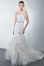 Illusions Style 3183 Organza, strapless, fit and flare bridal gown with asymmetrical ruching and an attached jeweled belt. The skirt on this wedding dress features intricate floral scroll motif with jewel encrusted organza flowers on side and attached train.
