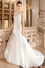 568 This glamorous, fit n flare, sleeveless gown features a tulle skirt, illusion neckline and shimmering bodice embellished with crystal beading. The low illusion back is finished with buttons and a sweep train.
