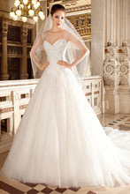 570 This shimmering beaded a-line gown features a sweetheart neckline with sheer, beaded cap sleeves and a low illusion back with button closure. The skirt features a basque waist and chapel train.