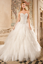 579 This unique ball gown features a magnificent bodice adorned with elaborate beaded embroidery with jeweling and a full multi-tiered tulle skirt. The back features a corset lace-up and chapel train.