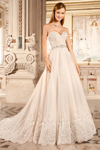 1479 This elegant, strapless gown with sweetheart neckline features a tulle, a-line skirt with a jeweled belt on the natural waist. The bodice and hem are adorned with embroidered lace that continues into the chapel train.