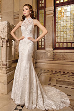 1487 This elegant, form fitting, chantilly lace gown features a sheer lace, high halter neckline embellished with beaded appliques, a striking sheer lace back with buttons and chapel train.