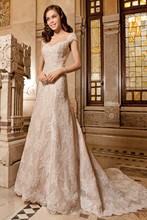 1494 This magnificent a-line gown is richly embellished with beaded alencon lace and features a sweetheart neckline and sculpted straps that flow into a low sheer back with button closure. Back is finished with a striking chapel train.