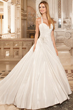 3212 This simple, taffeta a-line gown with a sweetheart neckline and ruched, wrap bodice features a side wrap skirt with jeweled applique and removable halter straps. The back is finished with a buttons and chapel train.