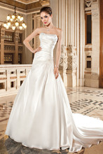 3225 This luxe organza, strapless, a-line gown features asymmetrical pleating on the bodice and beaded applique on hip. The back features a chapel length train.