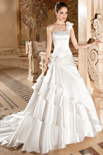 3227 This romantic luxe organza gown features flowers on one shoulder and a draped, multi-tiered skirt with flowers flowing into a chapel train. The back features a lace-up closure.