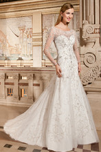 4328 This beaded tulle fitted a-line gown features a sweetheart silhoutte with a sheer beaded overlay on the neckline and long sheer, beaded sleeves. The low back features a button closure and semi-chapel train.