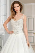 210 This sparkling full tulle gown with a v-neckline and basque waist features a jeweled bodice embellished with crystal beading. The high illusion back is adorned with a delicate design of beaded embroidery with button closure. The skirt features a chapel train.