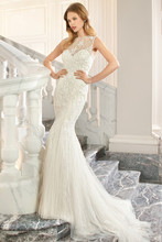 216 This sultry, old Hollywood inspired form-fitting gown is richly embellished with magnificent beaded embroidery and a high beaded illusion neckline. The low back features a high beaded illusion overlay with button closure and sweep train.