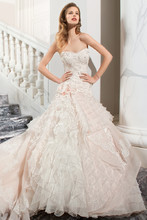 224 This unique strapless, gown features a lace bodice with three-dimensional flowers, a dropped waist and multi-tiered organza skirt with ruffles and accents of lace. The lace-up back features a chapel length train.