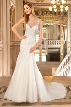 261 This sophisticated, tulle fit n flare gown features a sweetheart silhouette with a sheer neckline. Delicate lace accentuates the neckline and low sheer back with button closure. The flared tulle skirt flows into a chapel train.