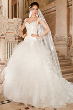 270 This romantic tulle gown features a sweetheart neckline dropped waist and lace-up closure. The bodice and sheer cap sleeves are embellished with embroidered lace. The multi-tiered full ruffled skirt flows into a chapel length train.