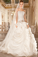 271 This striking, strapless gown features a dropped waist with lace-up back and a magnificent bodice embellished with opulent beaded embroidery. The organza skirt features a unique design of intricate scrolls and pick-ups continuing throughout the chapel train.