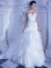 553 Strapless, Tulle, fit n' flare bridal gowns with a Sweetheart neckline and a-symmetrical pleating with jeweled beading and lace-up back. This wedding dress features a multi layered handkerchief skirt with sprays of beading and attached Chapel train.