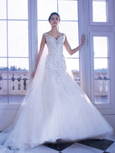 560 Beaded tulle ball gown wedding dress with a dramatic V-neckline, spaghetti straps and plunging back. The sparkling tulle skirt on this bridal gown features a Chapel train.