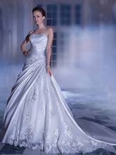 4322 Satin, Strapless, A-line wedding gown with a-symmetrical pleating on bodice and split skirt. This bridal dress is embellished with beaded Venice appliqués. Skirt features a side insert of beaded appliqués over tulle and attached Chapel train. Back is finished with a corset lace-up.
