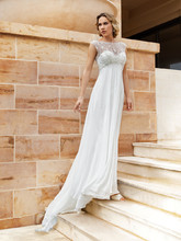 187 Chiffon destination wedding gown with a Sweetheart neckline and sleeveless sheer beaded overlay with a low V-back and buttons. The flowing A-line skirt on this bridal dress features a Chapel train.