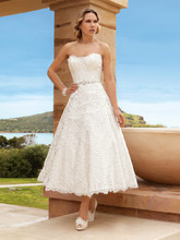 192 Chantilly lace, Strapless, A-line, Cocktail length destination wedding dress with jeweled trim on waist. This bridal dress features a scalloped neckline and hem.