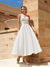 195 Taffeta, Strapless, A-line Cocktail length destination wedding dress with a Sweetheart neckline, ruched, wrap bodice. The belt on this bridal dress has a jeweled appliqué on waist.