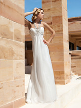 196 Chiffon, A-line destination wedding gown with a ruched Empire bodice with beading and jeweled halter Strap. The skirt on this bridal dress features a Sweep train.