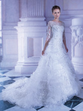 258 Tulle, A-line wedding gown with shimmering beaded lace embroidery, high sheer neck, ¾ length sleeves and ruffles with sprays of beading on skirt. The high sheer back on this bridal dress features buttons and ruffled, attached train.