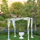 Our White Birch and Mahogany Table were draped in Chiffon. Then silk rose petals were draped on top and ivy was wound down and across the poles.