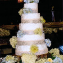 Vintage Wedding Cake - White rustic buttercream. Borders are vintage lace over satin ribbon. Light blue and green hydrangeas complete the design. Cake sits on a log plateau flanked by light blue and green hydrangeas and large cream colored marigolds.