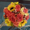 A Bridal Bouquet with an explosion of Fall Colors including Yellow Sunflowers, Orange Roses in various shades, Brown Roses and Berry Sprigs!