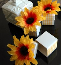 Sunflower Wedding Favor Boxes Perfect for a spring wedding or garden affair! These adorable sunflower favors feature a crisp white box wrapped in gingham ribbon and topped with a sunflower. Fill them with your favorite candy or treat for an added special touch! Advantage Bridal is pleased to offer fast shipping and a low price guarantee.