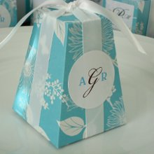"The pedestal favor box now comes in the most pretty pearlized silver floral and leaf pattern, adorned with playful butterflies. Inside, there is a lovely coordinated stripe pattern. Perfect for every occasion, you can fill with delicious edibles, wrap with elegant satin ribbon, personalize with a monogram label or tag, and give! Your guests will be ""a flutter"" when they see these beautiful favors waiting for them. Shown here with our Round Monogram Favor Label. Ribbon is not included. For a personal touch, add a label for an additional charge! Choose from our 3 Monogram layouts. Please enter your monogram text the way you would like it to be printed. For example, first name initial, last name initial, first name initial. This is made from a strong medium weight (65-70lb) cardstock for sturdiness and is able to hold up to 1 pound of goodies when put together. Box measures 2 1/2""w x 2 1/2""l x 3 1/4""h"