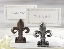"Looking for a classic and elegant favor? The fleur-de-lis has been the epitome of European elegance for centuries, and this acclaimed design adds distinction and elegance wherever it appears. These ""Fleur-de-Lis"" Place Card/Photo Holder will do the same for your next event. Fast shipping and a low price guarantee make it an even more attractive favor! Features and facts: -Finely detailed, resin fleur-de-lis has a slit at the top for place card or photo -Matching place card with fleur-de-lis motif included -Holder measures 2""h x 1"" w -Sold in a set of four bronze or pewter antique finish"